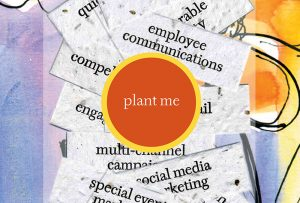 "Orange sticker showing the words ""plant me."" The strips of paper underneath the sticker are printed on paper embedded with seeds. Graphic design by Carolyn Porter of Porterfolio, Inc."